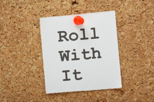 The phrase Roll With It on a cork notice board