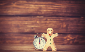 Cookie man and retro alarm clock on wooden background
