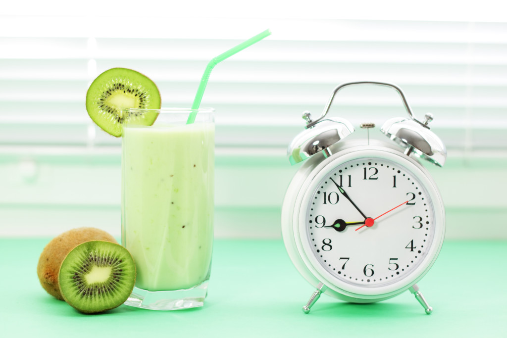 Kiwi juice in a glass and alarm clock on a light background